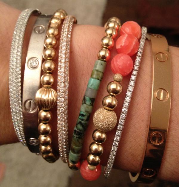 An arm party featuring Cartier Love Bracelets