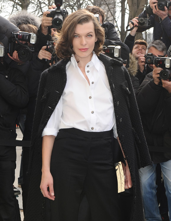 Milla Jovovich carrying a Chanel box clutch in gold at the Chanel Fall 2013 Show