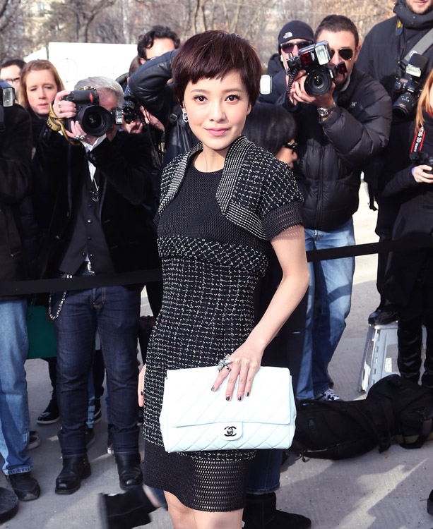 Amber Kuo carrying a white Chanel flap bag at the Chanel Fall 2013 show