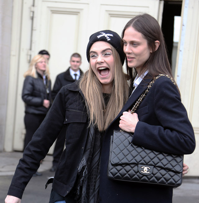 Models Cara Delevigne and Aymeline Valade with a Chanel bag at the Chanel Fall 2013 show