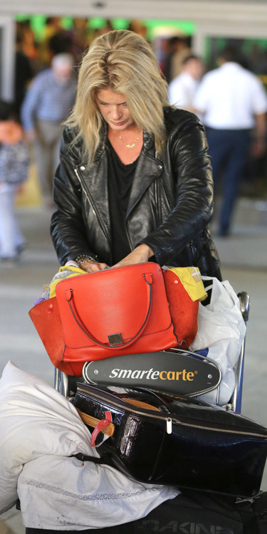 Rachel Hunter carries a red Celine Zipper Trapeze bag at the airport (1)