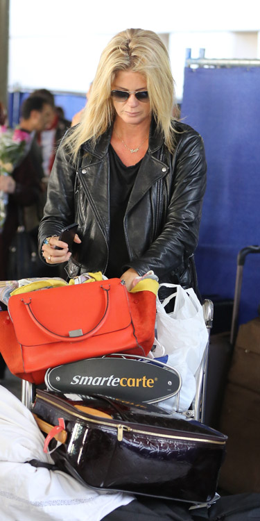 Rachel Hunter carries a red Celine Zipper Trapeze bag at the airport (4)