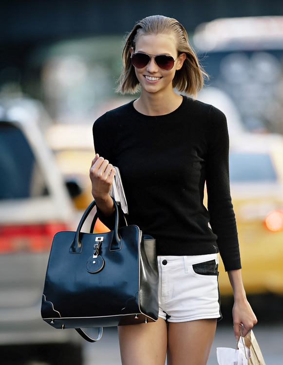 Fashion model Karlie Kloss seen wearing two tone denim shorts and converse sneakers while hailing a taxi cab in NYC