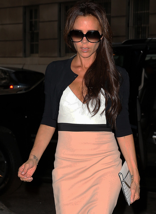 Fashion designer Victoria Beckham, wearing a nude pencil skirt with a white top and sweater, arrives at a press presentation for her fashion line on the Upper East Side in New York City