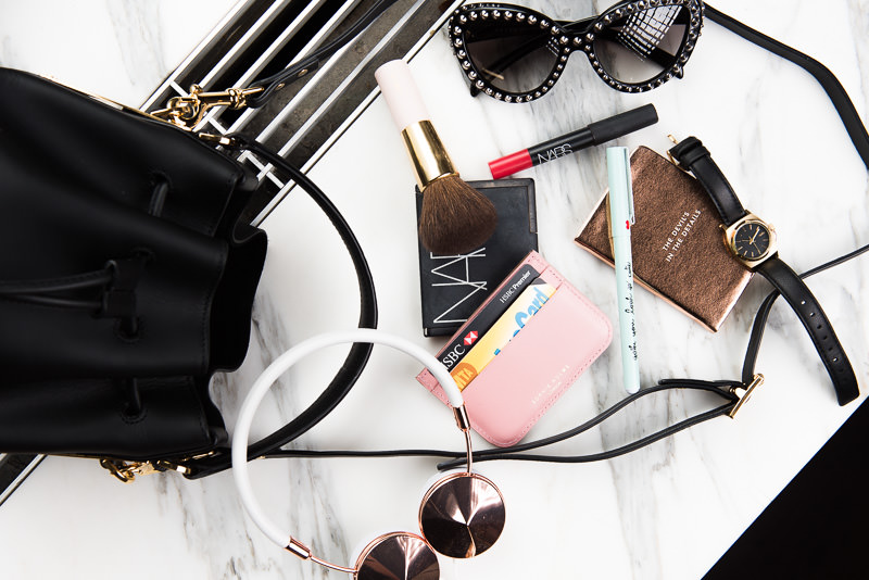 ban.do Sweet Talk Pen Set, $140. Kate Spade New York Devil in the Details Mini Notebook, $14. Frends Layla Headphones, $150. Nixon Small Time Teller Watch, $95. Sophie Hulme Card Holder, $140. Sophie Hulme Small Drawstring Bucket Bag, $825. J.W. Anderson Beach Bodice Top, $855. Prada Studded Cat Eye Sunglasses, $565. Mother Candice Swanepoel + Mother Stunner Jeans, $220. Alexander Wang Luca Mid Heel Pumps, $450