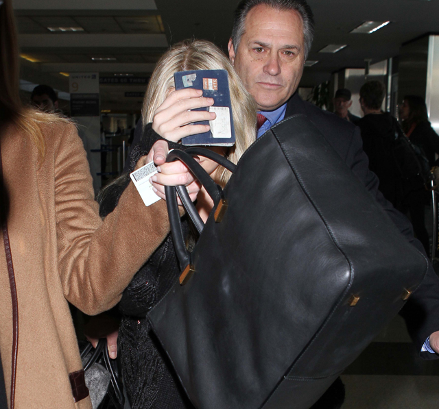 Actress and fashion designer Ashley Olson covers up by holding her American passport at LAX