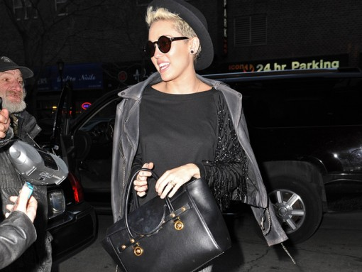 Miley Cyrus wears a black and white outfit including houndstooth leggings, a glitzy black top and Creepers