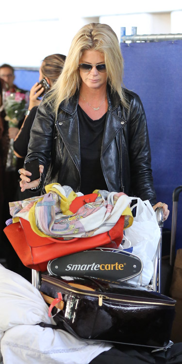 Rachel Hunter carries a red Celine Zipper Trapeze bag at the airport (3)