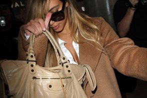 Kim Kardashian Shields Herself with a Balenciaga Bag at the Airport