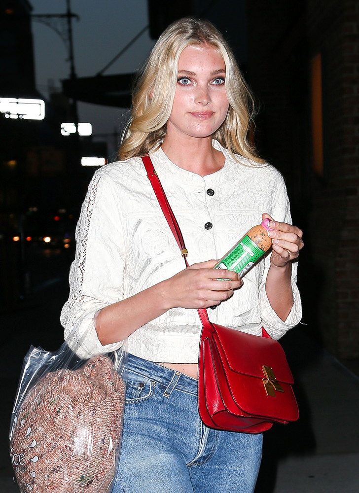 Elsa Hosk smiles as holding her juice while walking around at night in New York City