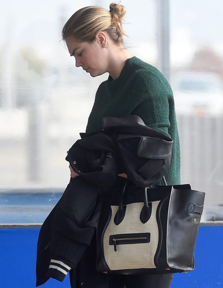 A make up free Kate Upton holds on to her Celine handbag while leaving JFK airport in Queens, New York
