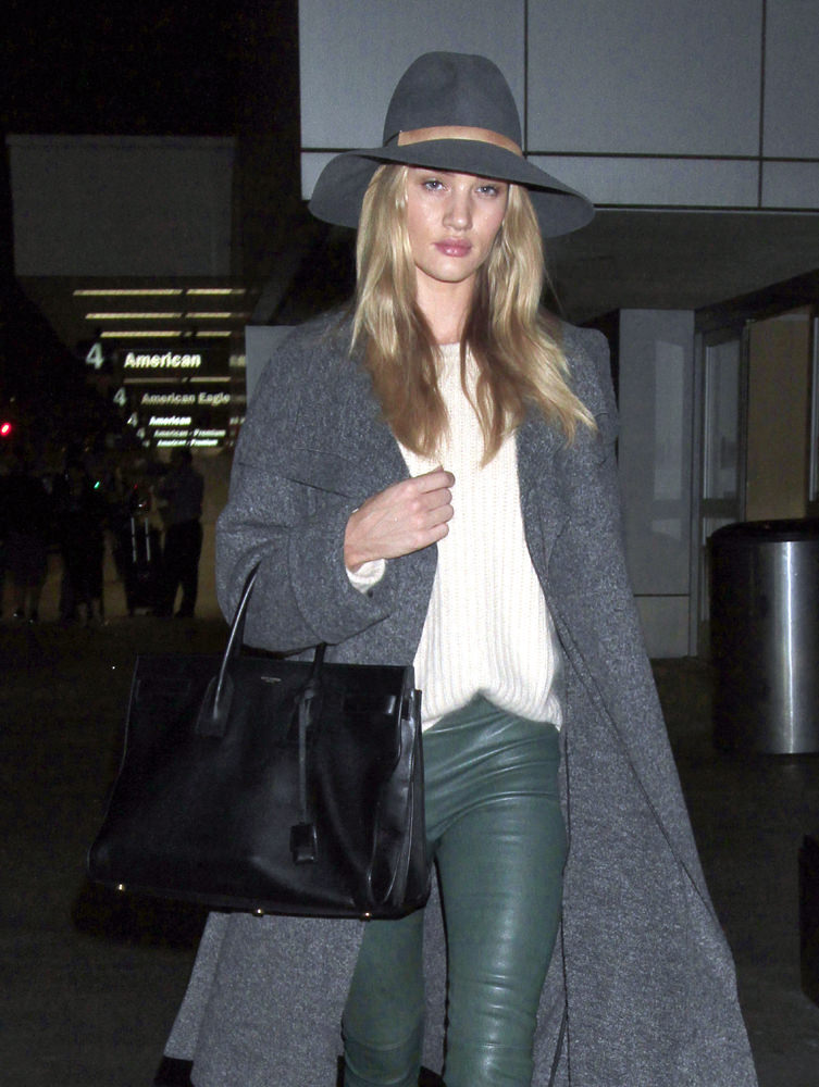 English model, Rosie Huntington-Whiteley looks flawless in green leather pants, boots, an overcoat, a sweater and a matching floppy hat
