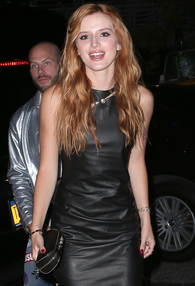 Bella Thorne is all smiles in a mini leather dress for the Versus Versace fashion show in New York City