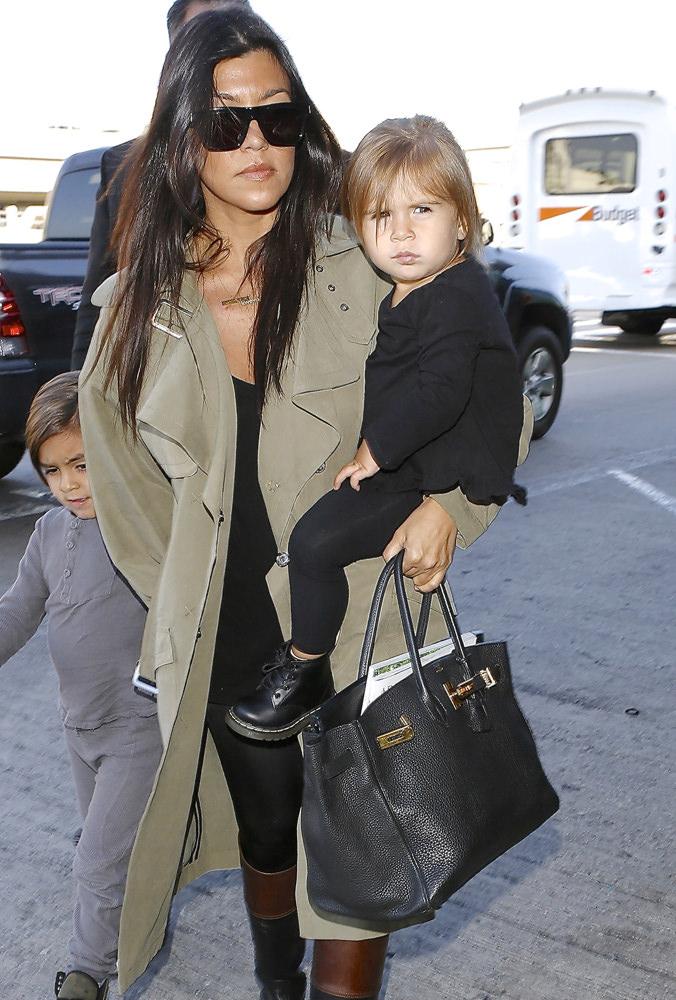 ba8ec5335e21fc Reality star Kourtney Kardashian and kids were seen departing LAX for Kim's  wedding