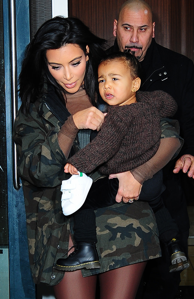 Kim Kardashian carries her daughter North West onto a show at New York Fashion Week