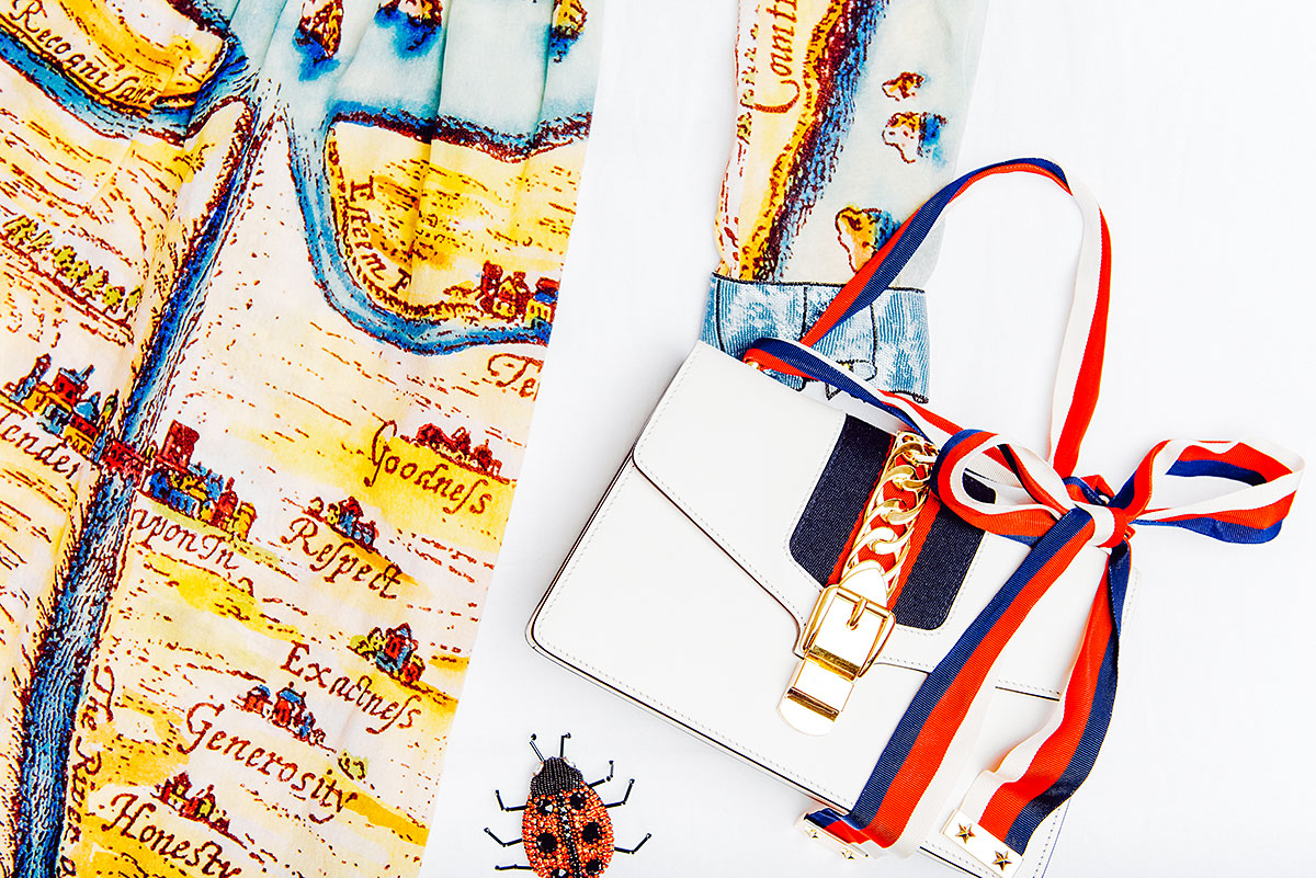 Gucci Sylvie Bag in Off-White, $2,490 via Gucci with the Gucci Carte de Tendre Print Dress, $4,200 via Gucci and Gucci Ladybug Brooch with Crystals, $580 via Gucci
